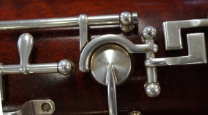 This is the Ab/Bb trill tone hole. It's surrounded by a mechanism that connects the thumb Ab key to the Ab tone hole on the front of the bassoon via a push rod.